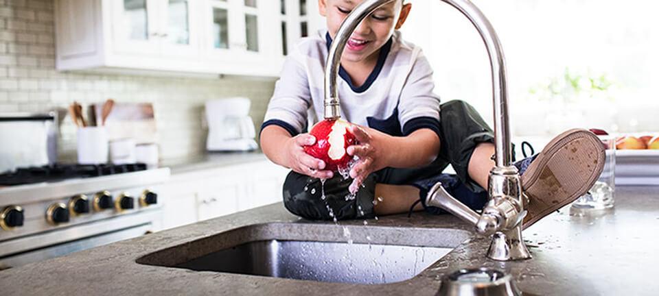 Boy washing apple in kitchen
